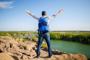 Image from back of young tourist with backpack with hands up against background of mountain landscape, lake