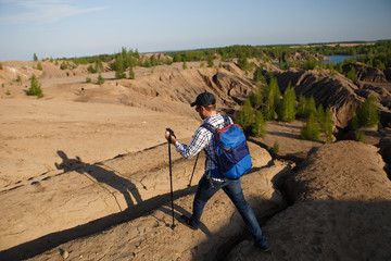 Photo of tourist man with walking sticks walking in mountainous area
