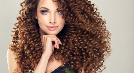 Spoed Fotobehang Kapsalon Brunette  girl with long  and   shiny curly  hair .  Beautiful  model woman  with wavy hairstyle