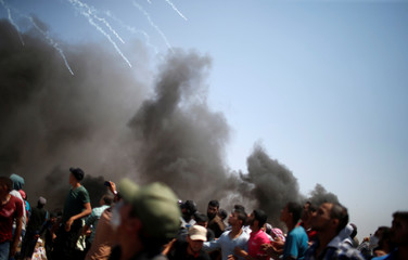 Tear gas canisters are fired by Israeli troops at Palestinian demonstrators during a protest marking al-Quds Day, (Jerusalem Day), at the Israel-Gaza border east of Gaza City