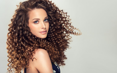Fotobehang Kapsalon Brunette girl with long and shiny curly hair . Beautiful model woman with wavy hairstyle