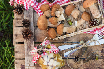 Raw white mushrooms, pine cones with dry decorations and silverware