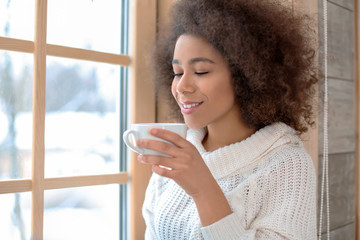 Beautiful African-American woman drinking tea near window