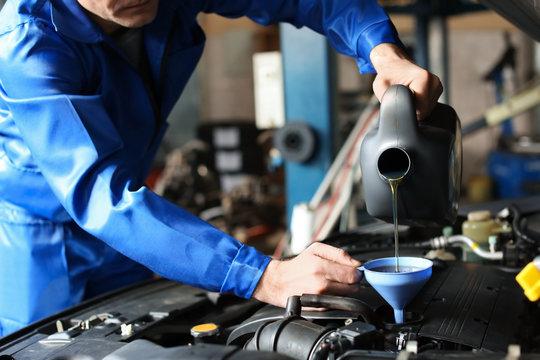 Male mechanic refilling car oil in service center
