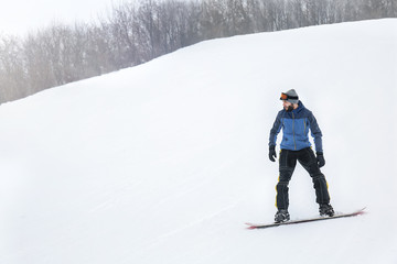 Male snowboarder on slope at winter resort