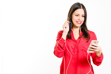 Young brunette woman in red clothes smiling typing message on smartphone holding headset, enjoying music, looking at camera - isolated on white background