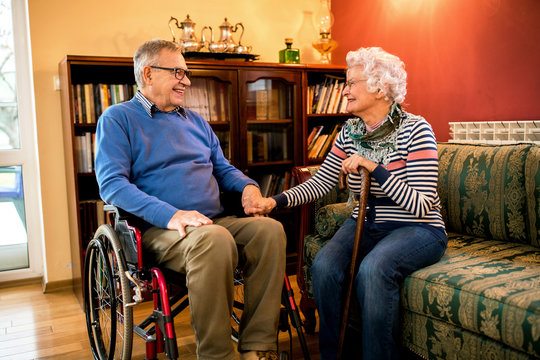 Smiling senior couple sitting and talking at home