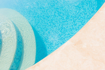 Clear blue water in the pool. Part of the pool closeup. Step into the water and finish the pool bottom slab-mosaic