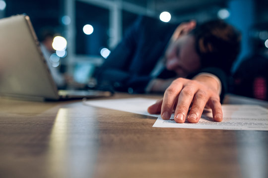Close up photo of sleeping mans hand on wooden desk. Hand of overworked businessman who stayed up until late night in office working behind laptop.