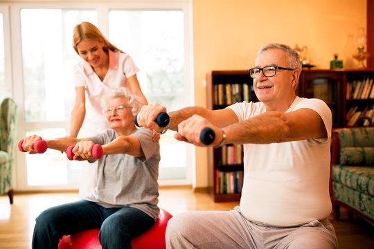 Nurse at nursing home helps senior people to doing exercises