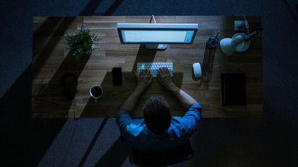 Top View of Male Programmer Working at His Desktop Computer at Night. His Table is Illuminated by Cold Blue Light From Outside.
