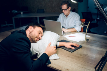Young man fell asleep in office at night. Good looking businessman resting his head on pillow on brown wooden office desk. His coworker sitting with laptop working in background.