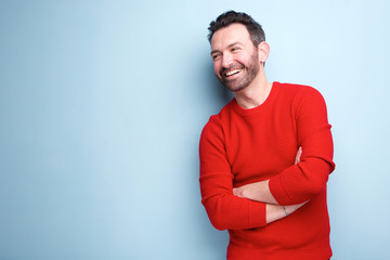 cheerful man with beard laughing against blue background