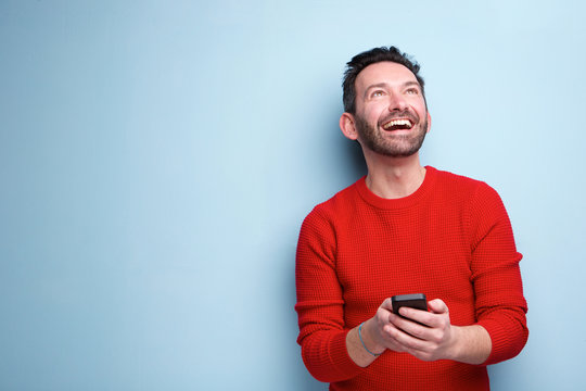 cheerful man with mobile phone looking up