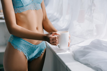 midsection view of slim african american girl in blue lingerie standing near window with cup of coffee