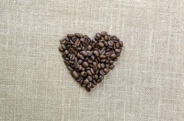 corazón de granos de cafe sobre arpillera