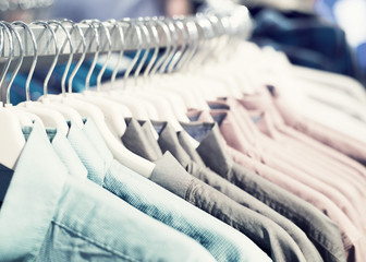 Mens shirts in different colors on hangers in shop, selective focus