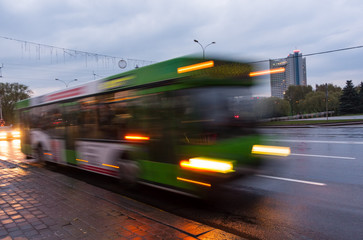 The motion of a blurred bus on the avenue at dusk.
