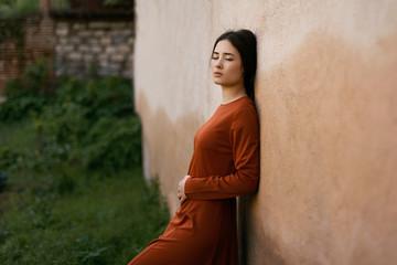 Sensual young woman standing at wall