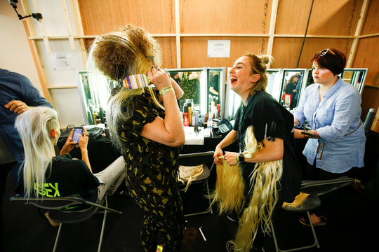 Makeup artists play around with hair extensions backstage of the Iceberg catwalk show at London Fashion Week Men's in London