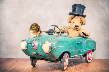 Teddy Bear in old antique cylinder hat driving rusty retro turquoise toy pedal car from circa 60s with classic brass klaxon in front concrete textured wall background. Vintage style filtered photo