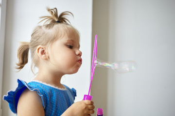 Profile picture of adorable little girl of Caucasian appearance pouting her lips while blowing soap bubbles against white wall background with copy space for your text or advertising information