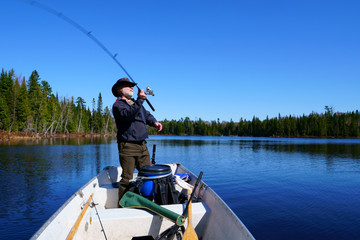 A peaceful caucasian man, 50's, wearing a white beard, a leather hat Australian style and a blue coat, is fishing in his boat on a lake with blue water by a beautiful, fresh, sunny morning.
