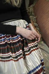 Multicolored pleated skirt on a thin girl