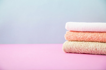 bath accessories - towels folded, stacked on a light, bright blue and pink background The concept of caring for yourself, your body. Copy space