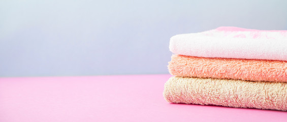 bath accessories - towels folded, stacked on a light, bright blue and pink background The concept of caring for yourself, your body. Copy space Banner concept