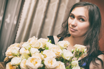 beautiful brunette with a bouquet of white roses