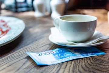 New Russian banknotes denominated in 2000 rubles for payment the bill in a restaurant on a wooden table under a white cup