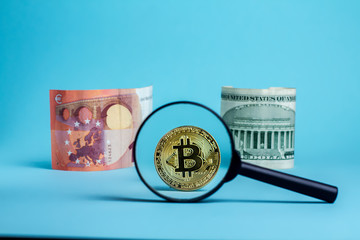 Magnifier glass with golden bitcoin coin. bitcoin against the dollar or euro on a blue background