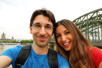 Happy traveling couple making selfie with Cologne City and Rhine river on the background, romantic mood. Couple of tourists in Cologne, Germany, Europe.