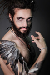 The image for halloween. A brutal guy with dreadlocks on a gray background. The guy with a thick beard. Hand the bird's wing. Feathers on hand. Fantasy
