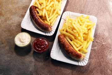 Grilled sausage served with french fries or fried potatoes with sausage
