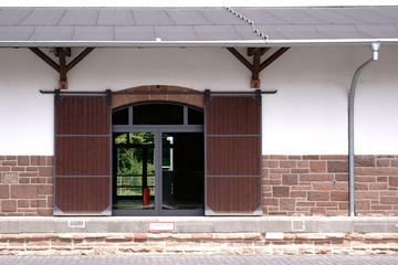 Holzschiebetür Güterbahnhof / Das Fachwerkgebäude eines Güterbahnhofes mit einer Holzschiebetür sowie einer Rampe.