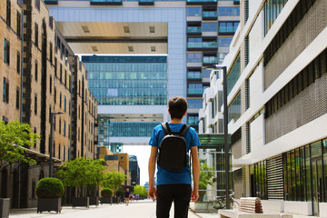 Rear view of a young man with backpack just arrived in big city and looking to modern buildings with perspectives and opportunities, Cologne city district, Germany
