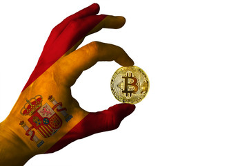 Bitcoin cryptocurrency Spain flag Isolated Golden Coin of Bitcoin in the Spanish flag hand between two fingers shows OK sign on a white background