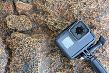 Black action camera against the background of rocks.