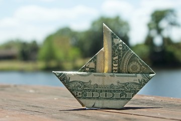 One dollar origami boat with blur background sitting on a wooden floor