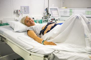Pregnant woman with ctg laying down on the hospital bed