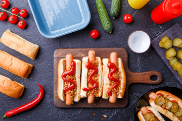 Picture on top of buns with sausages on cutting board, on table with cucumbers