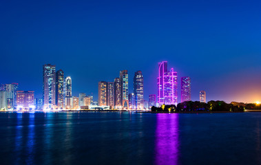 Sharjah waterfront cityscape in UAE at blue hour