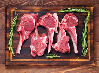 Raw lamb cutlets on bone on dark brown wooden background, lamb ribs, top view.