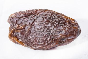 dried dates on a white background,  product of the date palm and cultivated since approximately 6000 B.C
