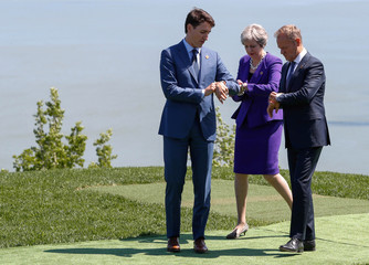 Leaders look at their watches as they pose for family photo at the G7 Summit in La Malbaie, Quebec