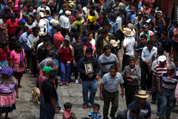 A man holds a picture of Maritza Nij, who died during the eruption of the Fuego volcano, during her funeral procession in Alotenango
