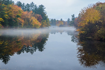 Early morning mist hangs  above a lake's waterline during a New England autumn.