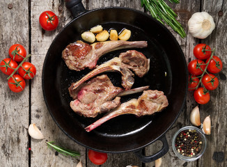 Roasted lamb ribs with rosemary, tomatoes and garlic on pan on dark old rustic wooden background, top view